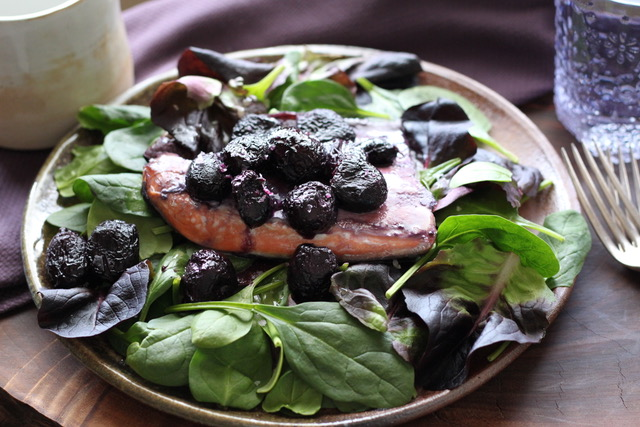 Pan-seared Salmon and caramelized grapes over leafy greens drizzled with homemade vinaigrette